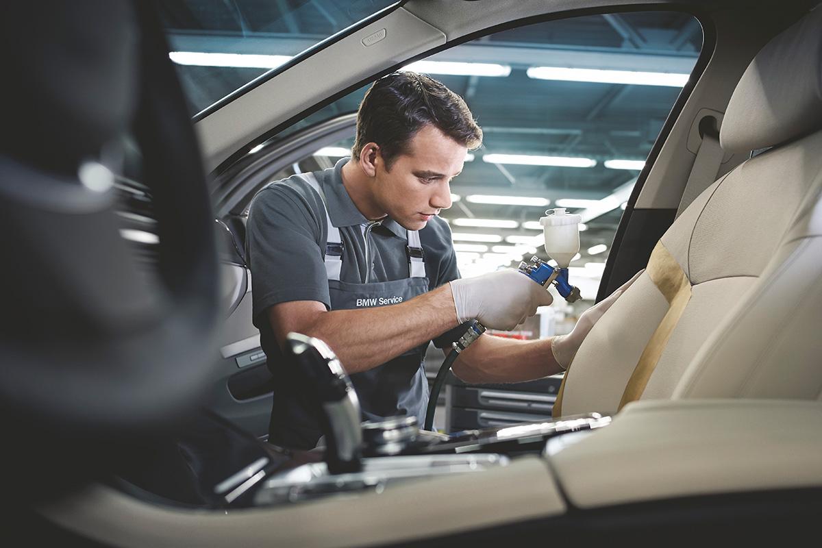 Huoltoammattilainen puhdistaa auton etuistuinta.